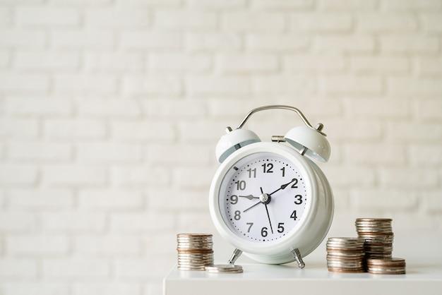 White retro alarm clock with coins on white brick wall background