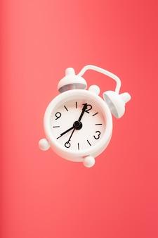 White retro style alarm clock in levitation isolated on pink background.
