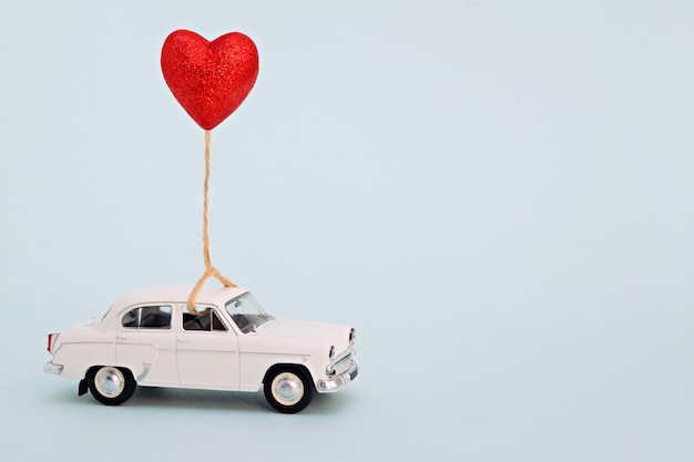 White retro toy car for valentines day with a heart-shaped ball.