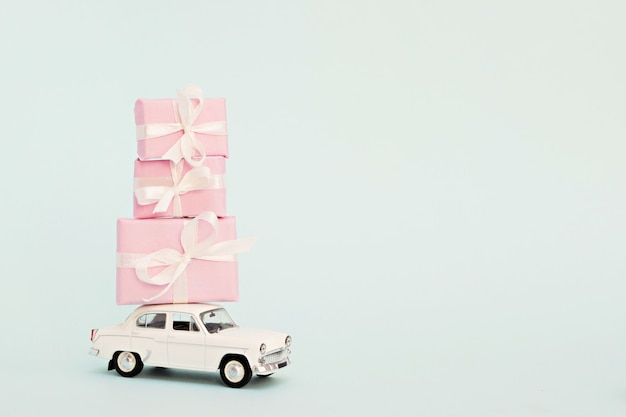 White retro toy car with pink gifts