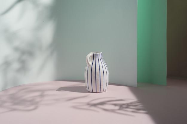 白いレトロな花瓶、葉の影とパステルカラーの背景に青いストライプ。インテリアデザインのコピースペース。