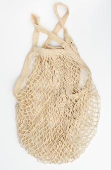 White  reusable string bag woven from thread on white background, zero waste