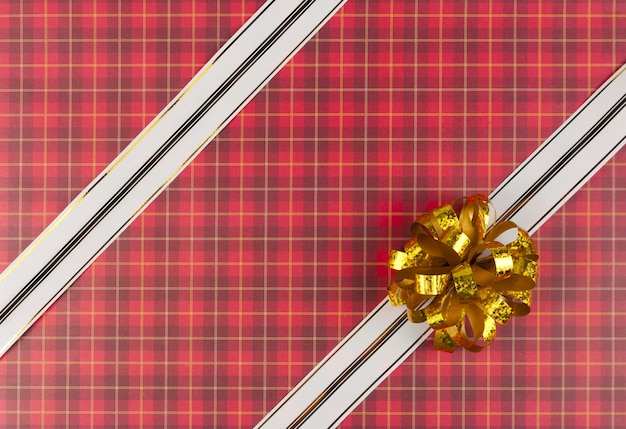 Белая лента и бант на красной подарочной бумаге