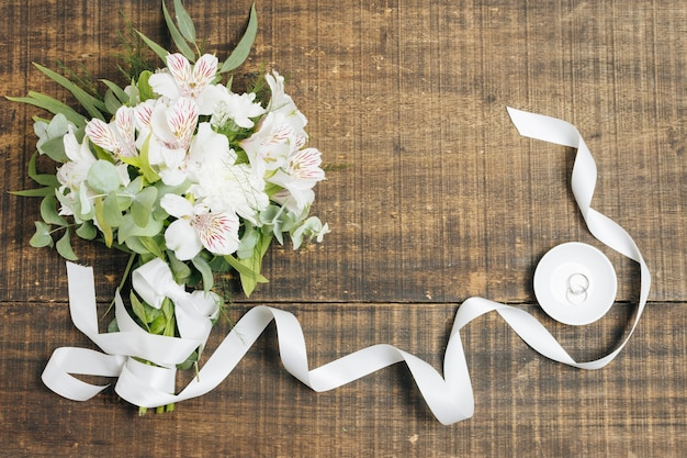 White ribbon and flower bouquet with wedding rings on plate over wooden desk