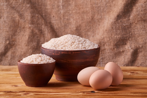 White rice in clay bowl on table and eggs on wood background