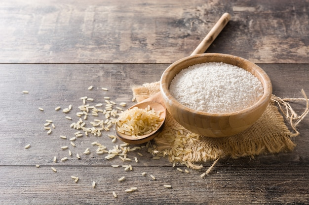 White rice flour in a bowl on wooden table, copy space