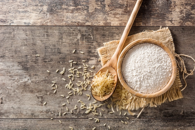 White rice flour in a bowl on wooden table, top view, copy space