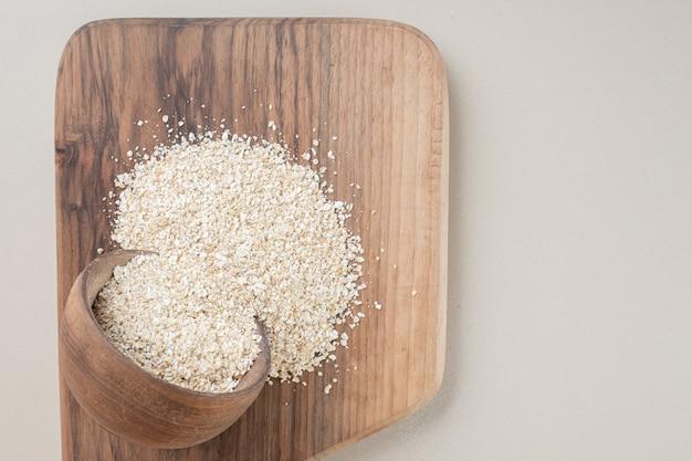 Белый рис в деревянной чашке на деревянном блюде.