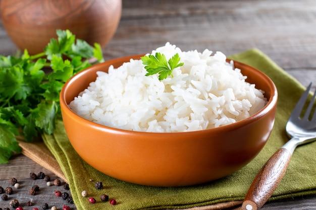 Белый рис в миске на деревянном столе