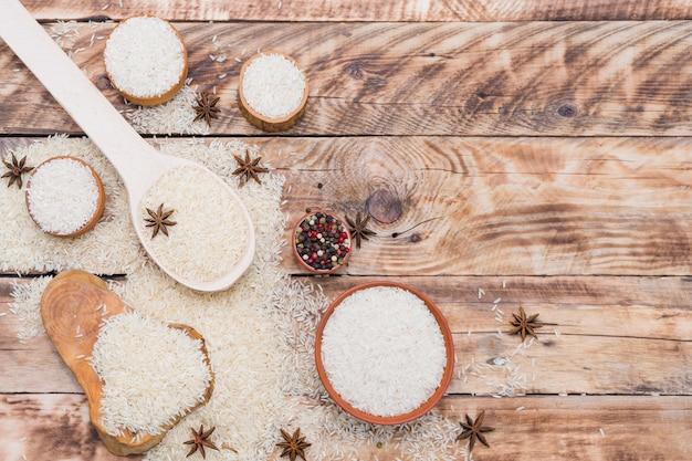 그릇에 흰 쌀; 질감 된 나무 표면에 건조 향신료와 숟가락과 나무 그 루터 기