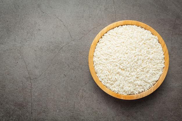 어두운 바닥에 작은 나무 접시 장소에 흰 쌀