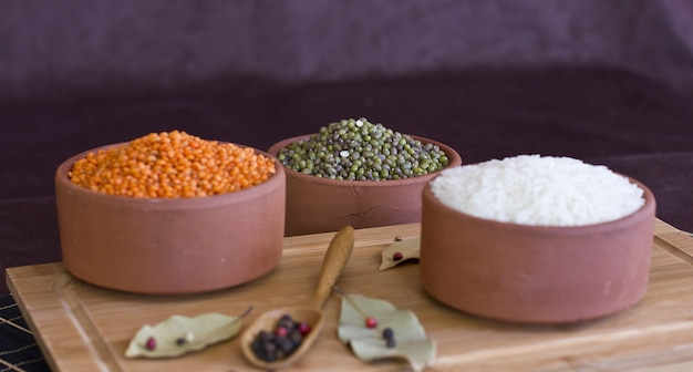 White rice, red lentils and green peas mache on wooden tray. bay