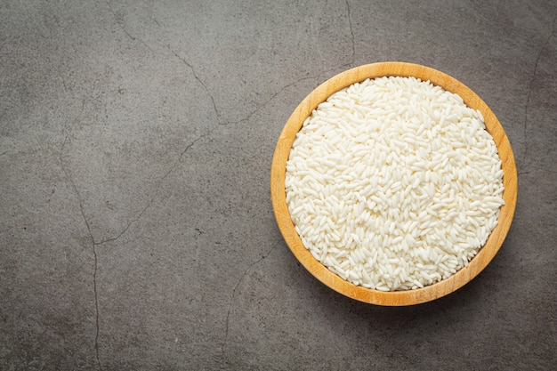 White rice on small wooden plate place on dark floor
