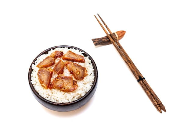 Белый рис с жареной свининой в черной миске на белом фоне