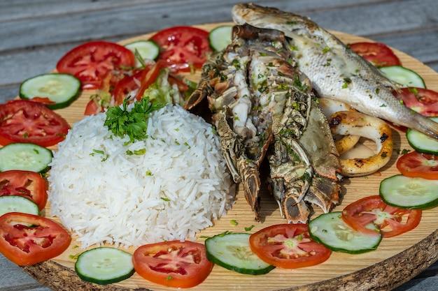 シーフードと野菜の白ご飯、クローズアップ。東アフリカ、タンザニア、ザンジバル島のレストランでの魚、イカ、エビ、米、トマト、キュウリ