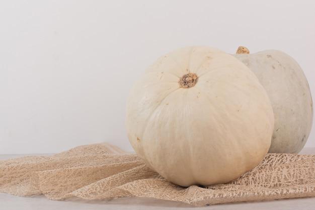 Zucca matura bianca su bianco con tela da imballaggio.