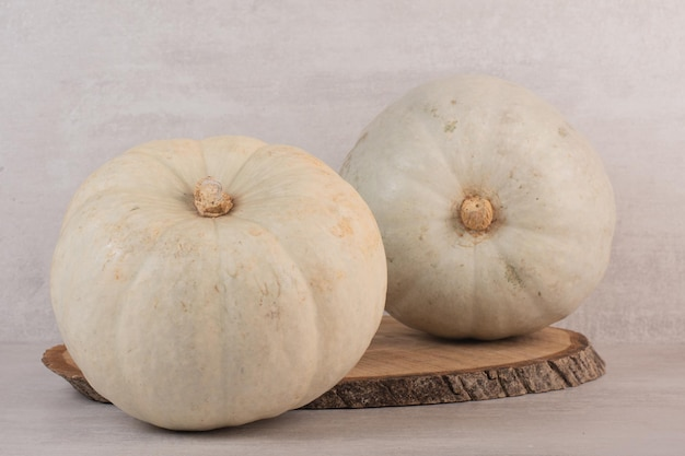 White ripe pumpkins on white table.