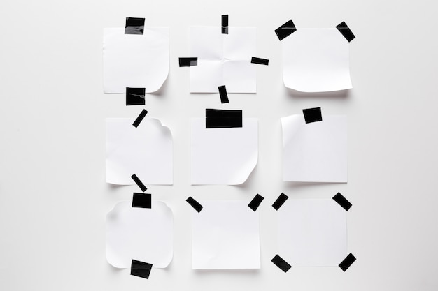 White ripped note, notebook paper stuck with black sticky tape isolated on white background