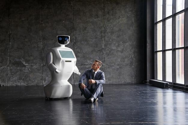 현대 로프트 사무실에서 양복에 흰색 로봇과 사업가