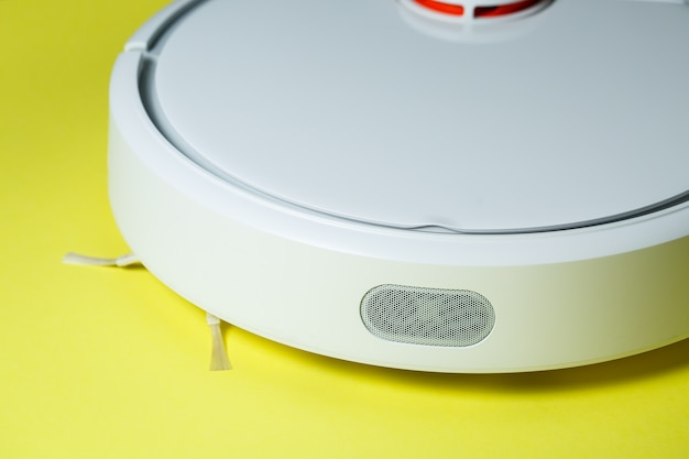 White robot cleaner for cleaning the house on a yellow background