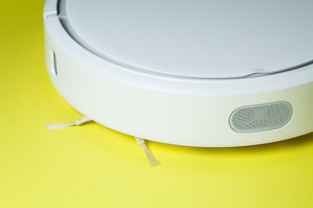 Белый робот-уборщик для уборки дома на желтом фоне