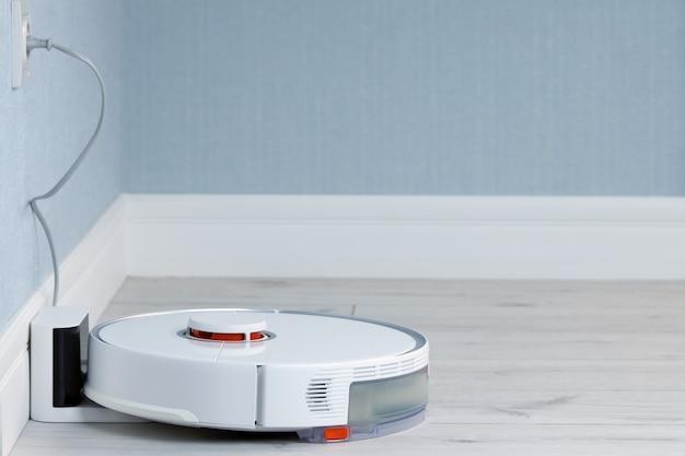 Белый робот-пылесос автоматически заряжается от зарядного устройства