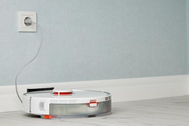 Белый робот-пылесос заряжает белую ламинатную интеллектуальную электронную домашнюю технику
