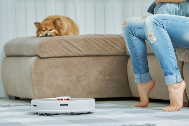 自動モードの白いロボット掃除機は、カーペットを効果的に掃除します