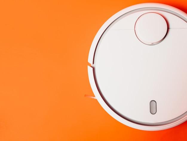 Белый пылесос робота изолированный на оранжевой предпосылке.