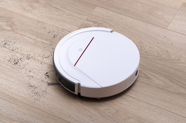 A white robot vacuum cleaner removes debris on the floor of the laminate.