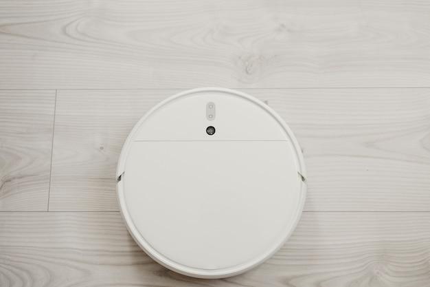 白いロボット掃除機が軽いラミネートフローリングを洗う
