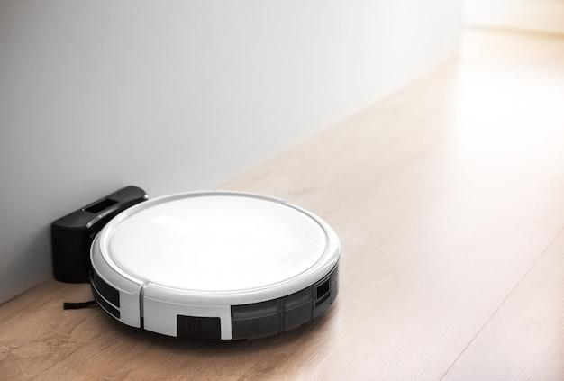 革新技術による人間の代わりに寝室、スマートホームと家の居間で自動掃除する白いロボット掃除機f