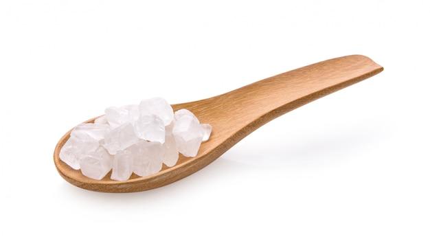 Белый камень сахара в деревянной ложкой на белой стене