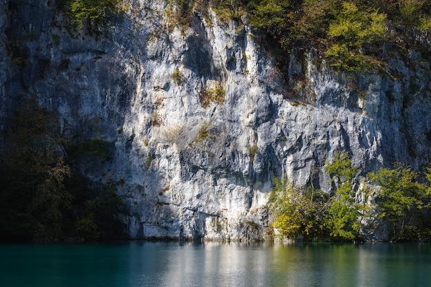 크로아티아의 플리트 비체 호수 근처 나무로 덮여 하얀 바위