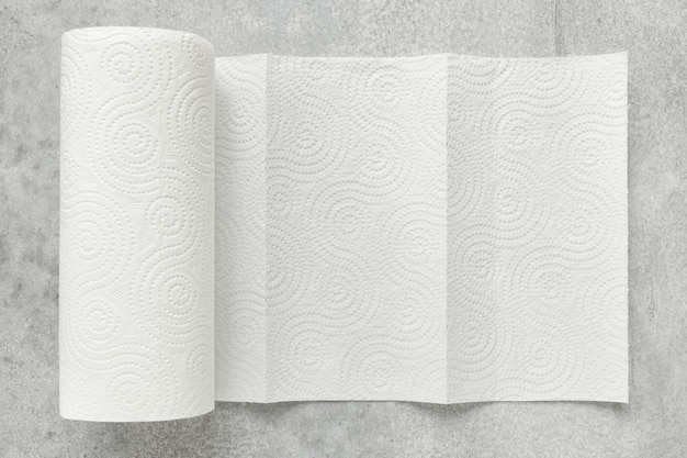 White roll of household paper towels on a gray background, shallow depth of sharpness