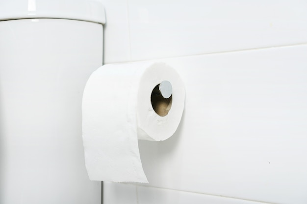 A white roll of soft toilet paper neatly hanging on chrome holder on a white bathroom wall. close up