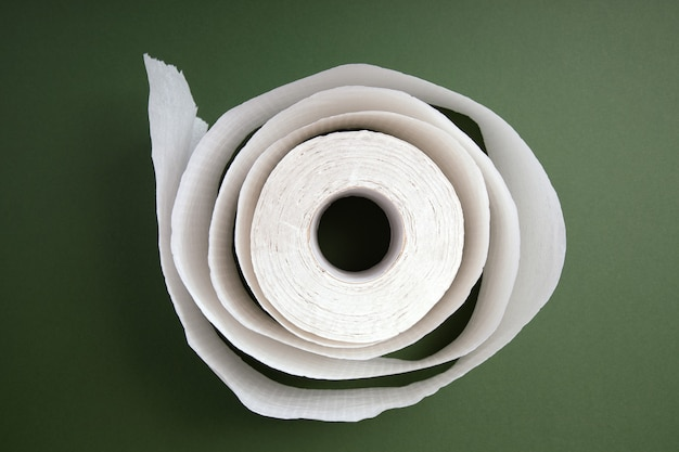 White roll of toilet paper over green background
