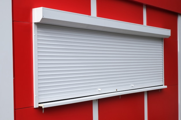 White roller shutters at a red kiosk.