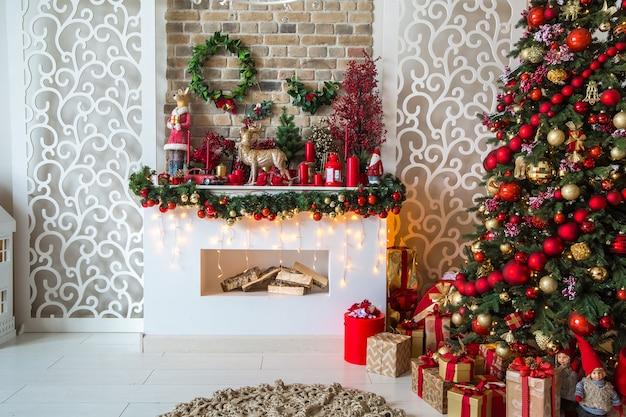 새해 트리 장식, 선물 상자 및 인공 벽난로가있는 붉은 색조의 화이트 룸 인테리어