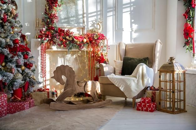 Интерьер белой комнаты в красных тонах с украшенной новогодней елкой, подарочными коробками и искусственным камином