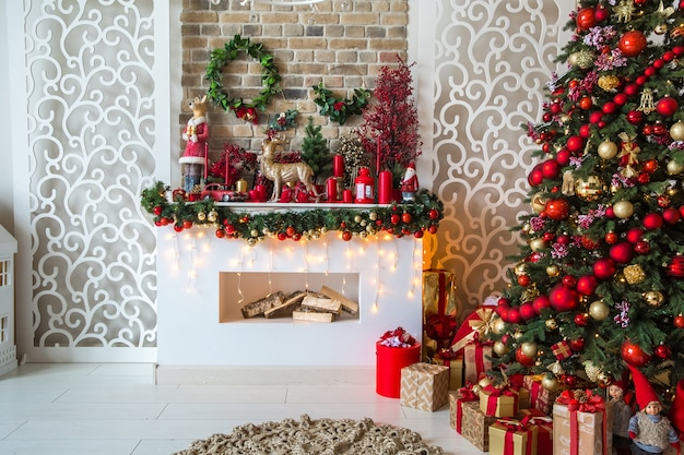 White room interior in red tones with new year tree decorated, present boxes and artificial fireplace
