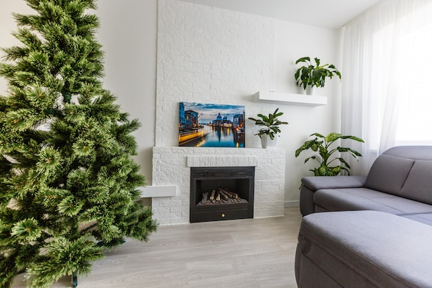 White room with white fireplace. white stone fireplace  christmas tree by the fireplace