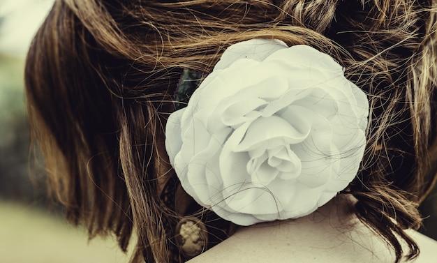 女性の髪に白いバラが付いている