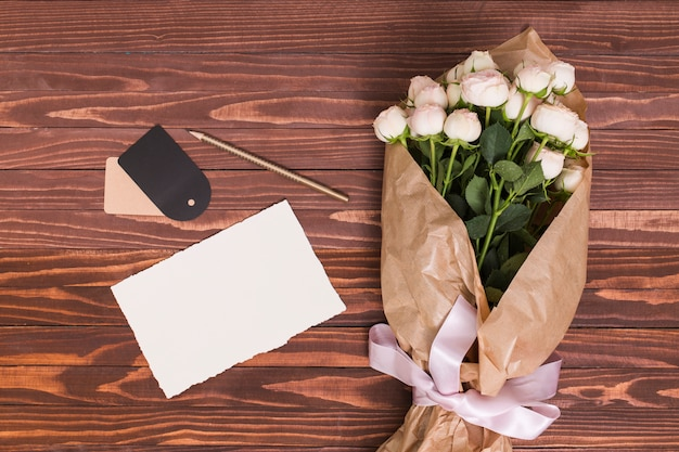 White rose bouquet; blank paper; pencil and price tag against wooden background