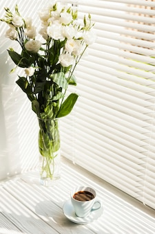 White rose flower vase and coffee cup near window blinds