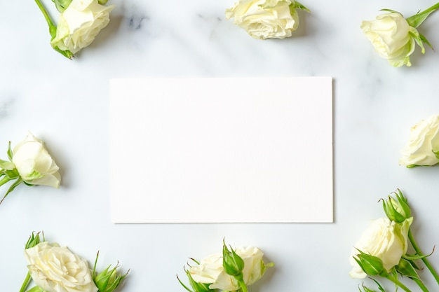 White rose frame and blank paper card on marble background, flat lay composition, top view, overhead.