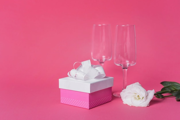 White rose; gift box and champagne flute glasses on pink backdrop