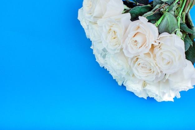 Белая роза с зелеными листьями на синем фоне