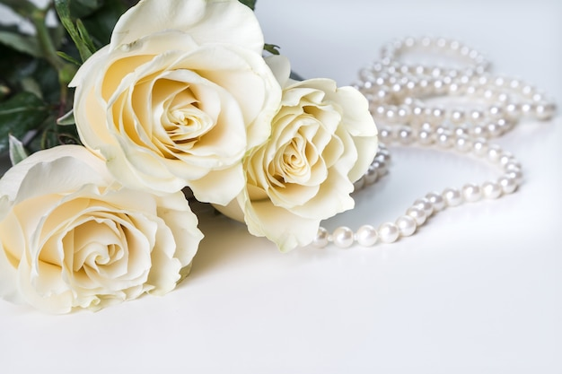 白い背景に白いバラと真珠のネックレス。