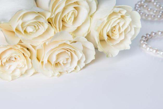 Белые розы и жемчужное ожерелье на белом фоне.